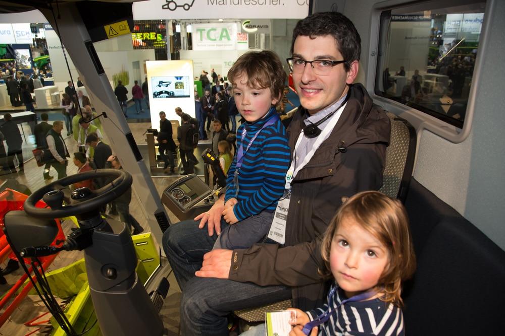 Familie sitzt in einem Claas Traktor auf der Agritechnica 2017